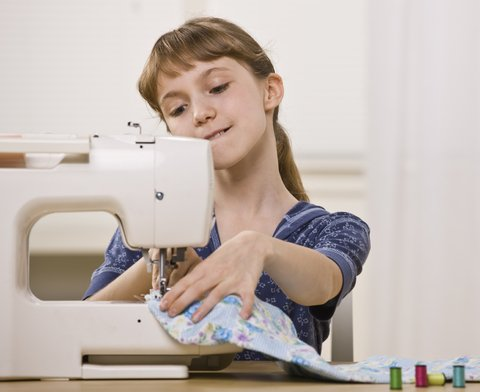 Young girl happily sewing on her refurbished sewing machines